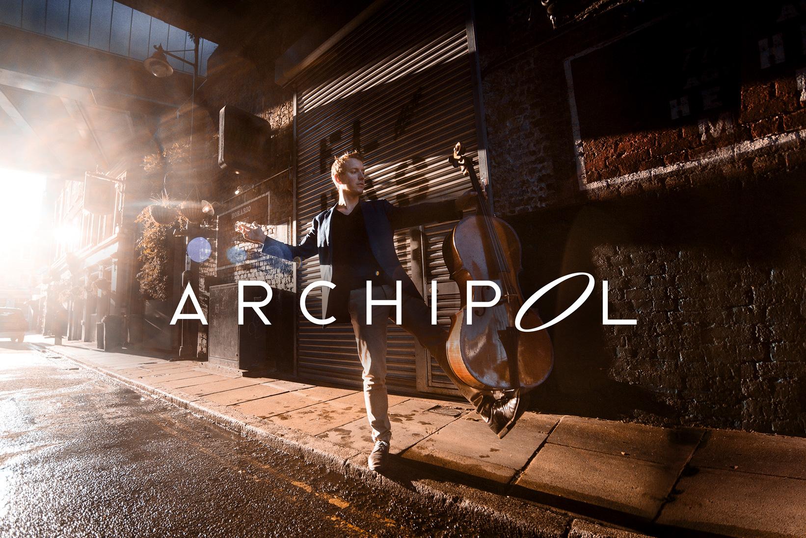 ArchiPol en costume de scène dans une rue, sur un pied, son violoncelle en équilibre sur l'autre